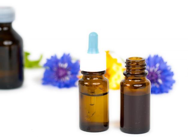 Olio essenziale di erbe in bottiglie di vetro isolato su sfondo bianco