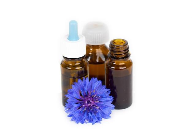 Olio essenziale di erbe in bottiglie di vetro con il fiore organico blu isolato