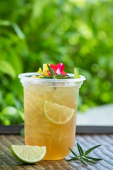 Cocktail di tè freddo alle erbe con fiori commestibili su una superficie di legno