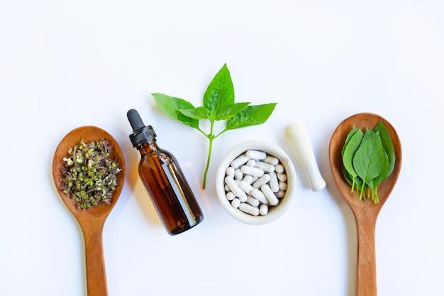 Pillole di medicina di erbe pillole e olio essenziale con foglie e fiori di basilico dolce