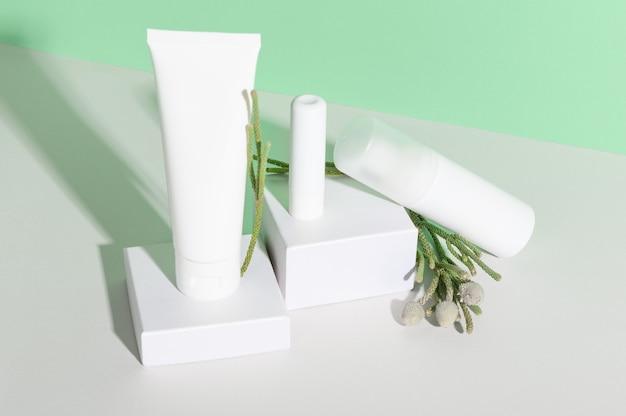 Composizione di bottiglie senza marchio in plastica bianca di cosmetici naturali a base di erbe.