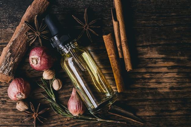 Estratto di olio di erbe per alimenti o aromi sulla decorazione della tavola in legno con erbe aromatiche.