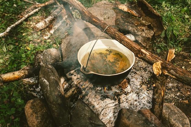 La tisana nel calderone si riscalda sul falò, circondata da pietre di cenere vicino all'erba verde. cucinare all'aria aperta. attività ricreative all'aperto. campeggio in natura. falò con fumo.