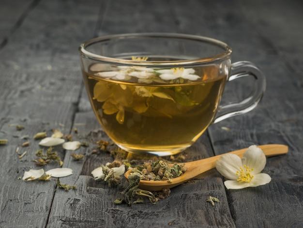 Tisana e fiori in un cucchiaio di legno e una tazza di tè in vetro. una bevanda tonificante che fa bene alla salute.
