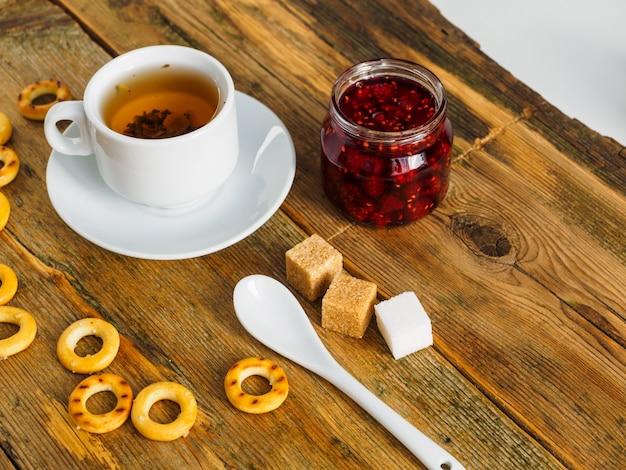 Tè alle erbe, marmellata di lamponi e bagel su un vecchio tavolo di legno.
