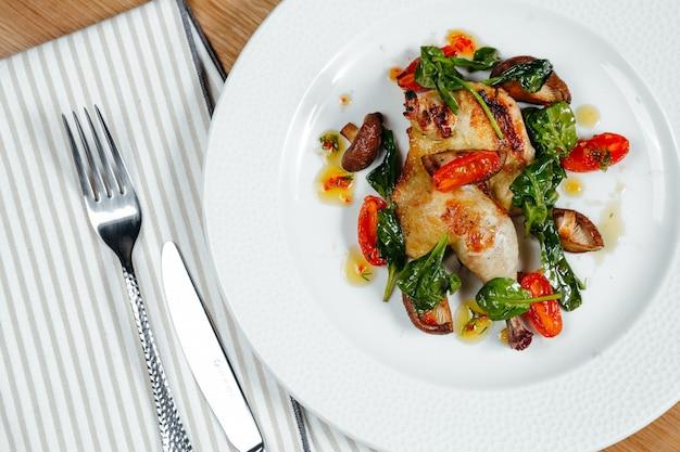 Pollo grigliato alle erbe e marinato, servito con funghi saltati, basilico e pomodori.