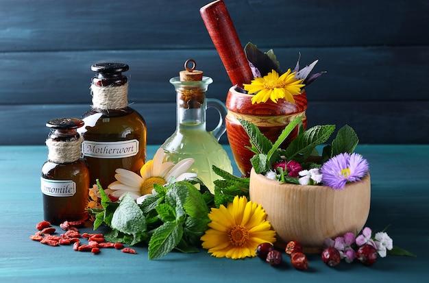 Erbe, bacche, fiori e pillole sulla tavola di legno di colore