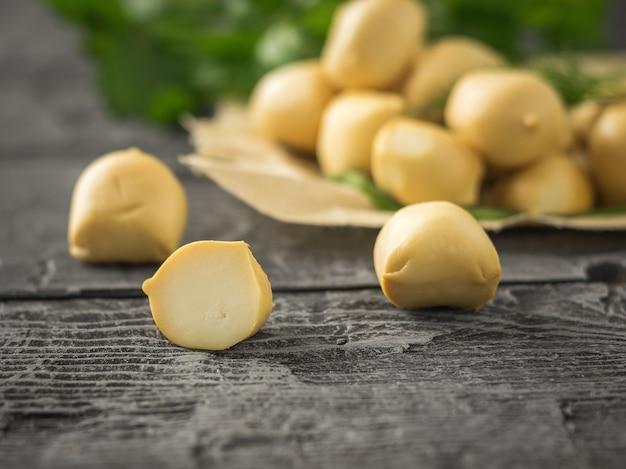 Erbe con palline di mozzarella appena fatta e aneto e prezzemolo su un tavolo di legno