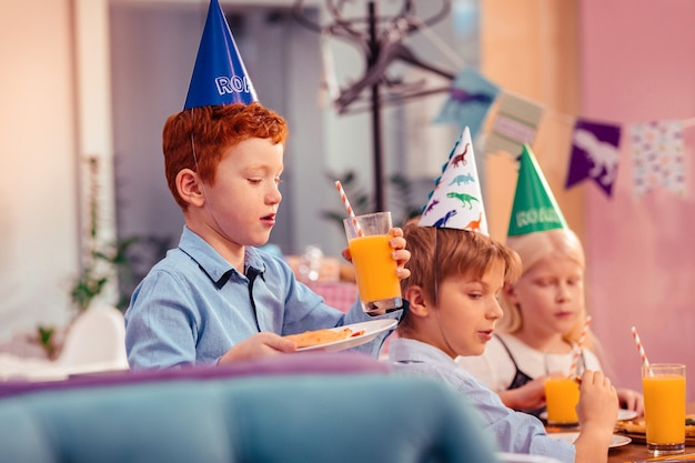 Eccomi qui. gruppo di compagni di classe che indossa cappelli di carta mentre era alla festa di compleanno