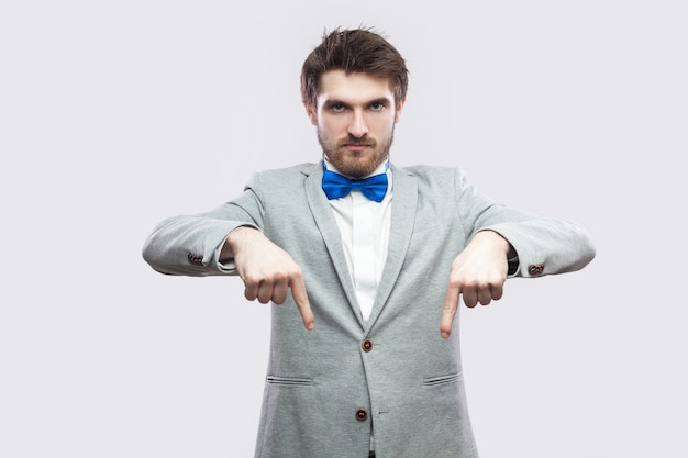 Qui e adesso. ritratto di un uomo barbuto bello prepotente serio in abito grigio casual e farfallino blu in piedi che punta e guarda la macchina fotografica. colpo dello studio al coperto, isolato su sfondo grigio chiaro.