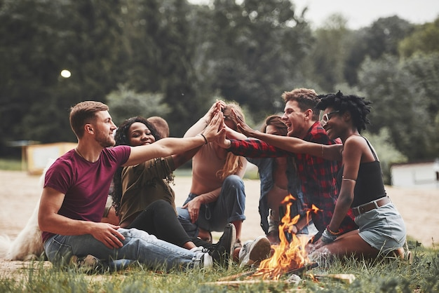 Qui ci incontriamo di nuovo. un gruppo di persone fa un picnic sulla spiaggia. gli amici si divertono durante il fine settimana.