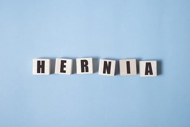 Parole di ernia da blocchi di legno con lettere, concetto di ernia condizione medica, sfondo bianco.