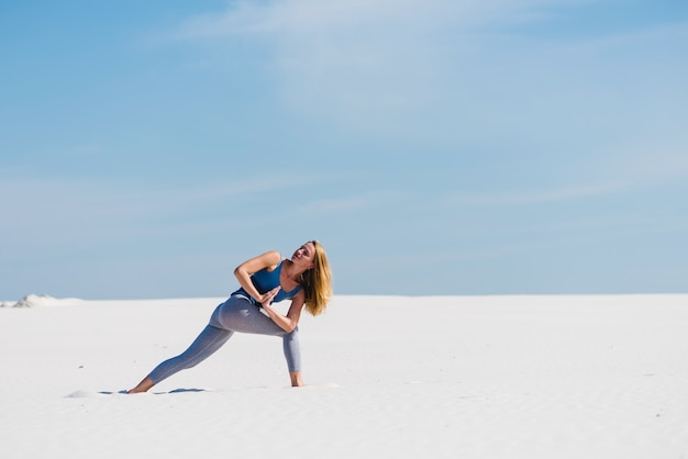 Yoga eroe posa variazione con namaste nel deserto