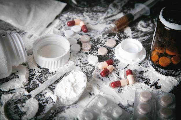 Eroina in polvere, pillole e siringhe su sfondo scuro.