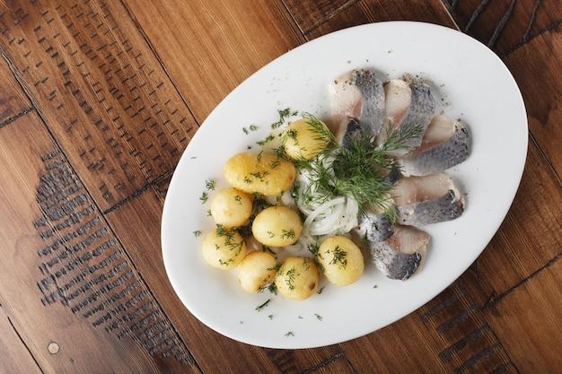 Pesce di aringa con polpette di patate novelle su un piatto bianco. fondo in legno.