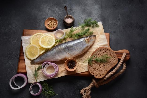 Pesce di aringa su tavola di legno con erbe di pepe cipolla rossa e limone su sfondo nero
