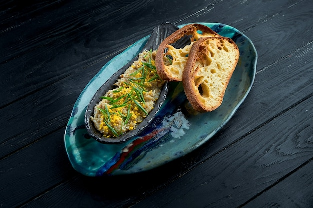 Forshmak di aringhe in un piatto blu, servito con crostini di pane su fondo di legno scuro.