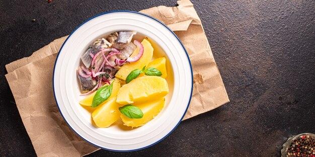 Aringhe patate pesce marinato con cipolle porzione fresca pronta da mangiare spuntino pasto sul tavolo