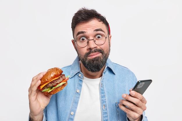 Esitante e imbarazzato uomo barbuto tiene in mano gustosi hamburger controlla newsfeed tramite smartphone mangia fast food sembra all'oscuro, indossa occhiali rotondi camicia di jeans