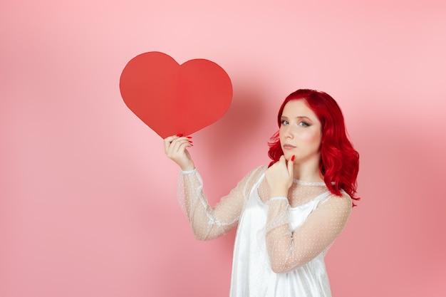 La donna esitante con i capelli rossi tiene un grande cuore rosso di carta e si strofina il mento con la mano