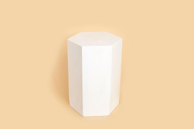 Figura geometrica a prisma esaconale di colore bianco che proietta la forma sul colore beige pastello