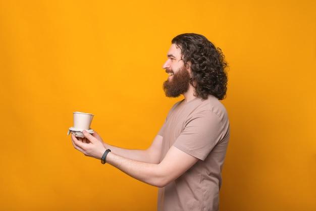 Ehi porta il tuo caffè con te, giovane allegro con i capelli ricci che dà due tazze di caffè per andare