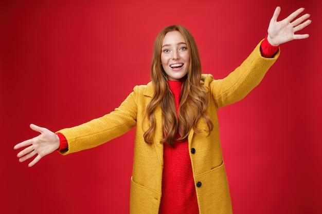 Ehi, vieni e abbracciami amico. affascinante femmina rossa giocosa ed emotiva che allunga i palmi in avanti per coccolare e salutare, dando un caloroso benvenuto sorridente che posa ampiamente in cappotto giallo sul muro rosso.