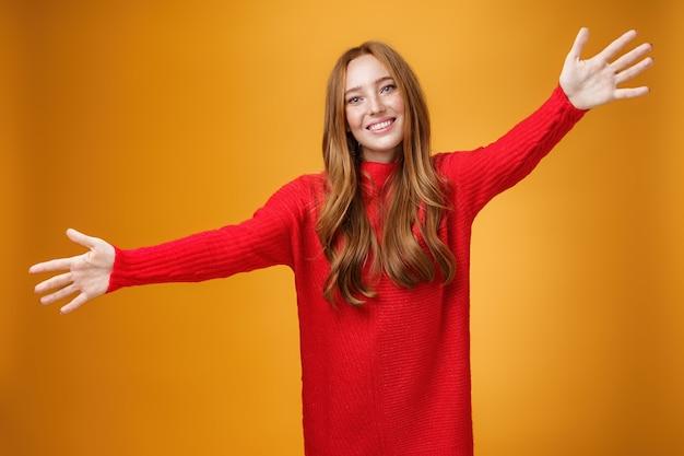 Ehi, vieni e abbracciami. ritratto di dolce sorella rossa femminile e carina in abito rosso a maglia che estende le mani verso la telecamera e sorride ampiamente dando un caloroso benvenuto, volendo coccole sul muro arancione