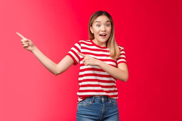Ehi, sbrigati, guarda. entusiasta eccitato carino biondo asiatico ragazza urbana che punta a sinistra mostrando offerte incredibili, alzare le sopracciglia entusiasta parlare fotocamera sorridente felice stand sfondo rosso impressionato