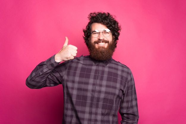 Ehi, mi piace, foto di un uomo hipster barbuto felice che mostra il pollice in su
