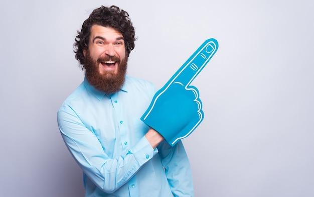 Ehi, guarda questo, uomo allegro che indica lontano con un guanto di schiuma blu a ventaglio