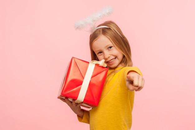 Ehi, questo regalo per te. ritratto di felice bambina zenzero con aureola angelica che abbraccia scatola avvolta e punta alla telecamera, scegliendo il fortunato vincitore per dare bonus, regalo. foto in studio al coperto, isolata