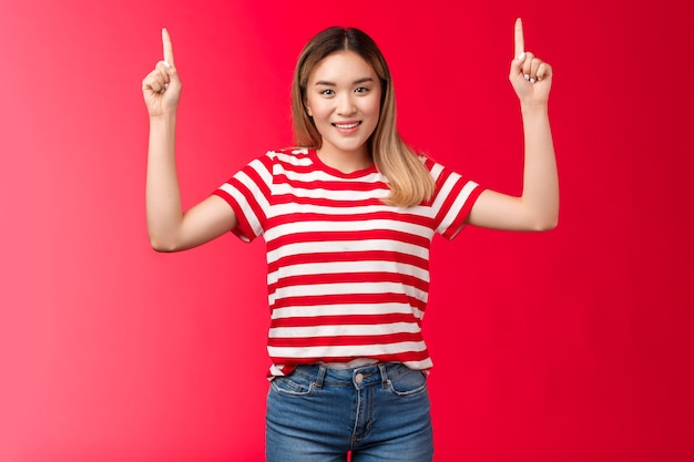 Ehi, andiamo. allegra bella ragazza asiatica che punta le mani in alto, mostrando promozione sorridente allegro, modello femminile propone un buon posto appendere pubblicità, in piedi sfondo rosso