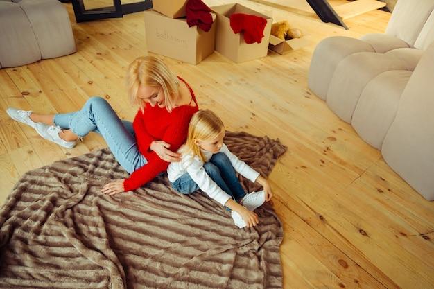 Ei, tu. carina persona di sesso femminile seduta sul pavimento e calmante sua figlia