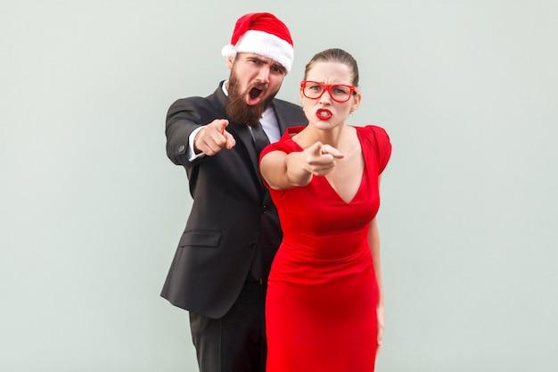 Ei, tu. seriamente uomo d'affari e donna che guardano la telecamera, puntano il dito e allerta. studio girato su muro grigio