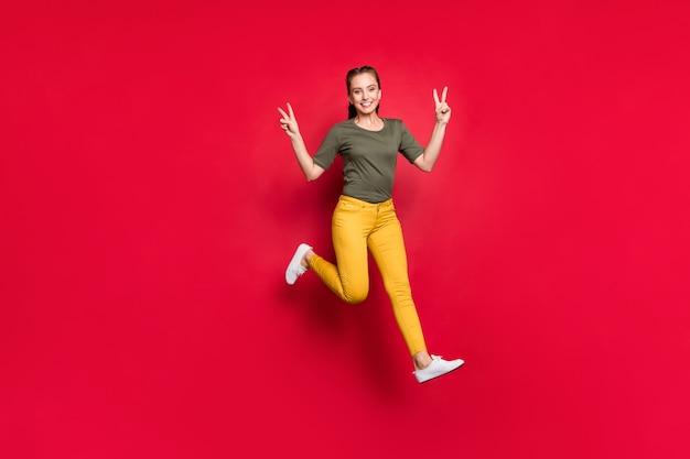Ciao a tutti! foto a figura intera di trecce lunghe di signora divertente millenaria che salta in alto mostrando simboli di segno di v indossare pantaloni gialli casual maglietta verde isolato sfondo di colore rosso