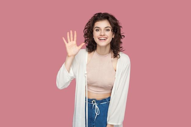 Ciao, felice di vederti. ritratto di bella giovane donna castana soddisfatta felice con l'acconciatura riccia nella condizione di stile casuale, esaminante macchina fotografica e saluto. girato in studio isolato su sfondo rosa.
