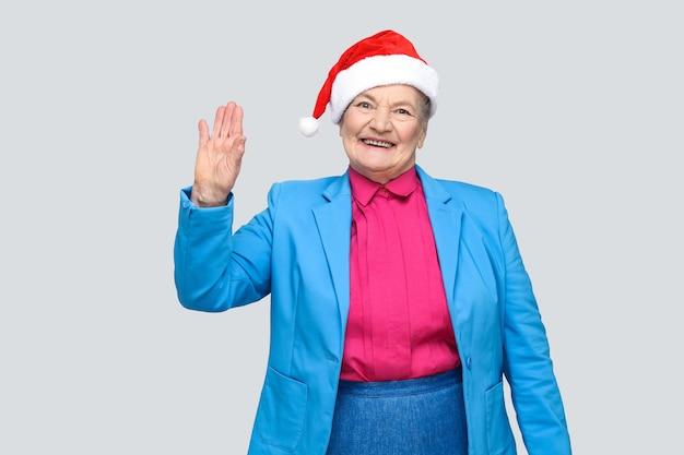 Ciao piacere di conoscerti. felice toothy sorridente colorato stile casual di età compresa tra donna con abito blu e berretto rosso di natale santa in piedi e guardando la fotocamera. indoor, girato in studio, isolato su sfondo grigio
