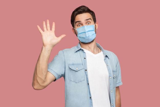 Ciao piacere di conoscerti. ritratto di giovane sorpreso con maschera medica chirurgica in camicia blu in piedi e guardando la telecamera con sorriso e saluto. foto in studio al coperto, isolata su sfondo rosa