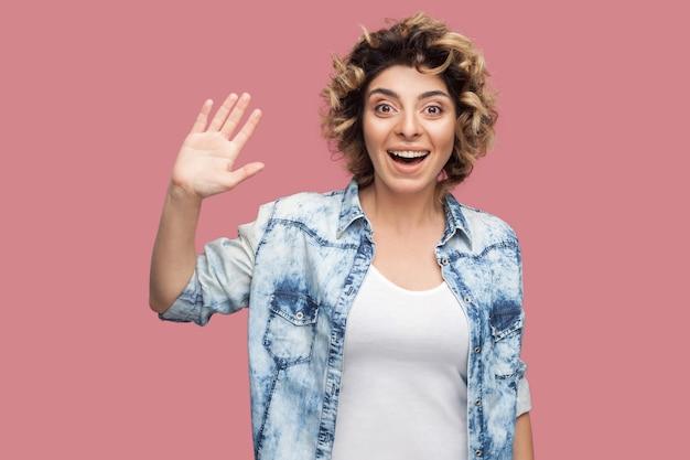 Ciao. ritratto di giovane donna felice sorpresa con l'acconciatura riccia in camicia blu casual in piedi, salutando, agitando la mano e guardando con un sorriso a trentadue denti. foto in studio al coperto, isolata su sfondo rosa