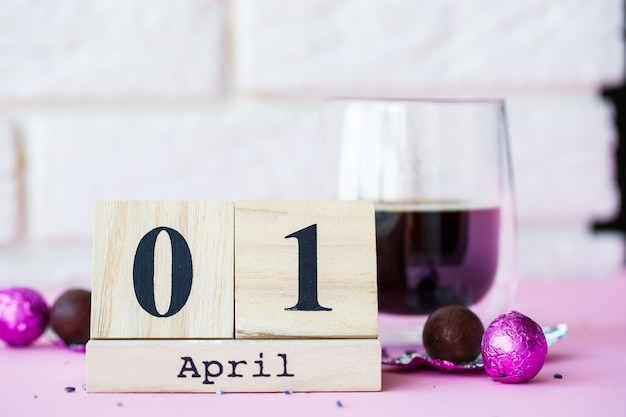 Ciao primavera. calendario in legno con data 1 aprile, su sfondo rosa. giornata mondiale della risata