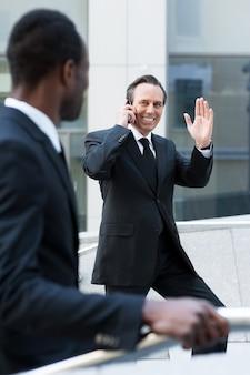 Ciao! uomo maturo allegro in abiti da cerimonia che sale le scale e saluta il suo collega