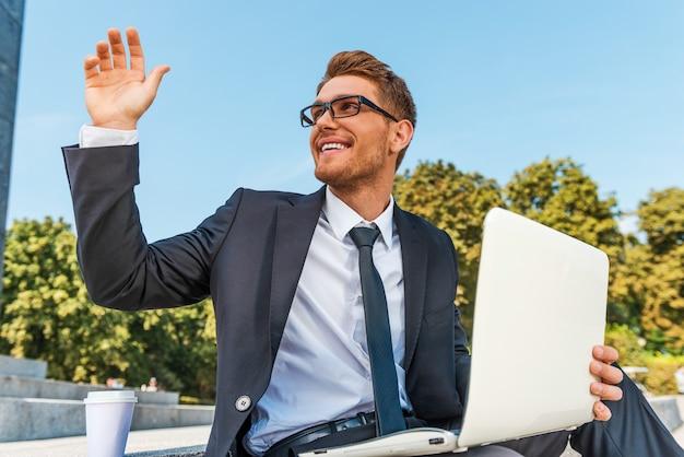 Ciao! inquadratura dal basso di un giovane allegro in abiti da cerimonia che tiene in mano un laptop e saluta qualcuno mentre è seduto all'aperto