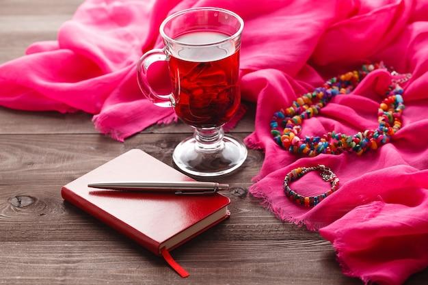 Tè di ibisco e scialle di seta rosa sul tavolo