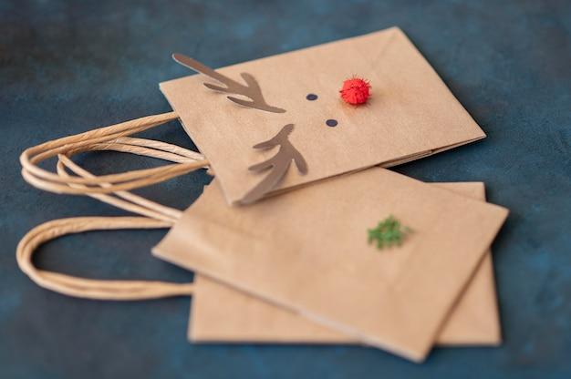 Alto angolo di adorabili renne decorate con sacchetti di carta natalizi