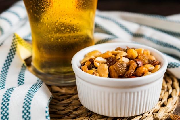 Alto angolo di noci assortite con un bicchiere di birra