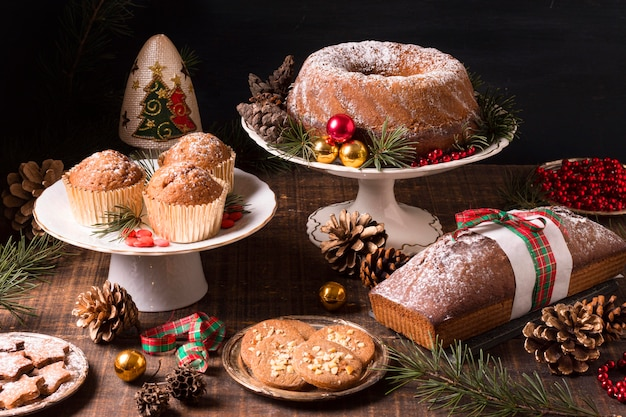 Alto angolo di assortimento di dolci natalizi con pigne e bacche rosse