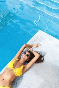 Alto angolo di bella donna castana con abbronzatura estiva dorata, sdraiata vicino alla piscina e sorridente in occhiali da sole e bikini.