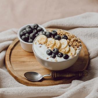 Alto angolo di colazione a letto con cereali e mirtilli
