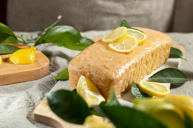 Alto angolo di torta con fette di limone e foglie